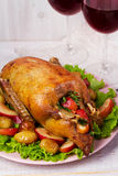 Canard de rôti avec la pomme de terre, les pommes, la salade, le thym et le romarin Deux glaces de vin rouge Images stock