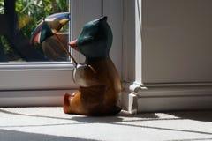 Canard en bois se reposant par une fenêtre Photo stock