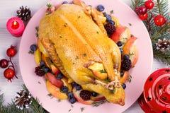 Canard entier avec des pommes, des baies et le thym Photo libre de droits