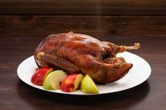 Canard rôti entier chaud avec les pommes fraîches sur la table en bois Photos stock
