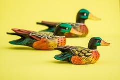 Canards en bois fabriqués à la main pour la décoration à la maison sur le fond jaune Images libres de droits