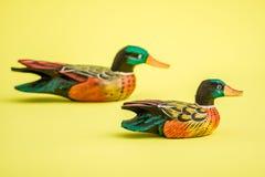 Canards en bois fabriqués à la main pour la décoration à la maison sur le fond jaune Photographie stock