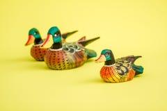 Canards en bois fabriqués à la main pour la décoration à la maison sur le fond jaune Images stock