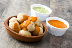 Canarian potatoes (papas arrugadas) with mojo sauce. On wooden table royalty free stock photography