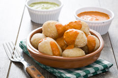 Canarian potatoes (papas arrugadas) with mojo sauce. On wooden table royalty free stock images