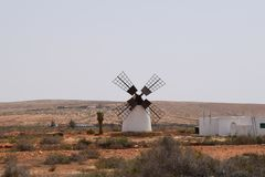 Canarian traditional windmill in Fuerteventura island. Traditional windmill. It is in the inland, on the vulcanic island Fuerteventura. White architecture stock images