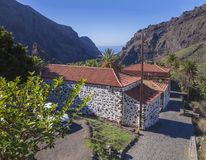 Tenerife view on old stone house in Masca village with palm tees, beatiful green sharp cliff, sea horizon and blue sky background Royalty Free Stock Photography