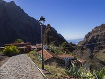 Canary Island, Tenerife  view on pitoresque Masca village with o. Ld stone houses, street lamp, cacti, beatiful green sharp hills, cliff, sea horizon and blue Royalty Free Stock Photos