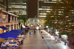 Canary Wharf ajusta la visión en luces de la noche con los oficinistas que se enfrían hacia fuera después de día laborable en caf Fotos de archivo