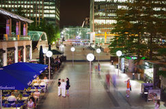 Canary Wharf ajusta la visión en luces de la noche con los oficinistas que se enfrían hacia fuera después de día laborable en caf Imagen de archivo libre de regalías