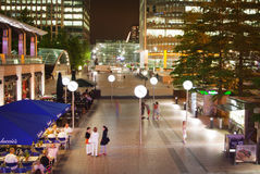 Canary Wharf ajustent la vue dans des lumières de nuit avec des employés de bureau refroidissant après jour ouvrable dans les caf Photographie stock libre de droits