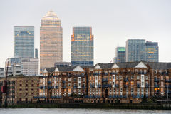 Canary Wharf, London, at dusk. Canary Wharf, London, England, UK, at dusk with some typical Thames waterfront residential buildings in the foreground Stock Image