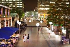 Canary Wharf quadrieren Ansicht in Nachtlichter mit den Büroangestellten, die heraus nach Arbeitstag in den lokalen Cafés und in  Lizenzfreie Stockfotografie