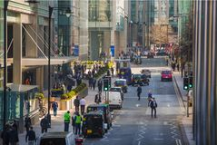 Canary Wharf street view with lols of walking business people and transport on the road. Business and modern life o. London, UK - March 15, 2017: Canary Wharf Stock Photo