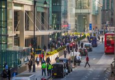 Canary Wharf street view with lols of walking business people and transport on the road. Business and modern life o. London, UK - March 15, 2017: Canary Wharf Stock Photos