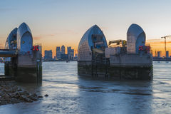 Canary wharf and Thames Barrier at dusk, London UK. LONDON, UK - JUNE 06, 2015: Thames Barrier with Canary Wharf in the distance at dusk, view across river Royalty Free Stock Photos