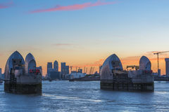 Canary wharf and Thames Barrier at dusk, London UK. LONDON, UK - JUNE 06, 2015: Thames Barrier with Canary Wharf in the distance at dusk, view across river Royalty Free Stock Photography