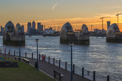 Canary wharf and Thames Barrier at dusk, London UK. LONDON, UK - JUNE 06, 2015: Thames Barrier with Canary Wharf in the distance at dusk, view across river Stock Images