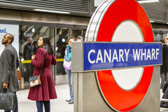 Canary Wharf underground sign with commuters waiting on a platfo Stock Photo