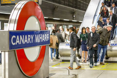 Canary Wharf underground sign with a crowd of commuters Stock Photography