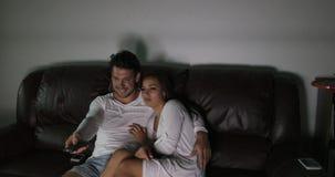 Canaux de changement de couples se reposant sur le divan regardant la TV programmer embrasser la communication de datation de par clips vidéos