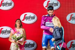 Canazei, Italy May 24, 2017: Fernando Gaviria, in purple jersey of the best sprinter. On the podium after a hard montain stage of Tour of Italy 2017 that Royalty Free Stock Photos