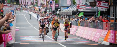 Canazei, Italy May 24, 2017: Professional Cyclist exhausted passes the finish line after a hard montain stage. Of Tour of Italy 2017 that finish in the center Stock Photos