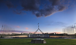 Canberra Parl 02. Australia Canberra acting as capital territory ACT Parliament building at sunset with illuminated facade and flagpoles Stock Photo