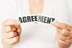 Cancel an agreement or dismiss a contract concept. With woman tearing apart a print-out of the word 'agreement royalty free stock photos