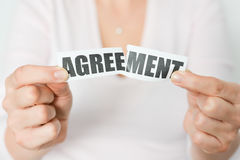 Cancel an agreement or dismiss a contract concept. With woman tearing apart a printout with the word 'agreement stock photography