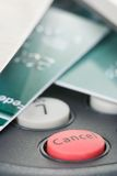 Cancel the transaction. Credit cards on pin pad card reader out of focus with attention on red cancel button Royalty Free Stock Photography