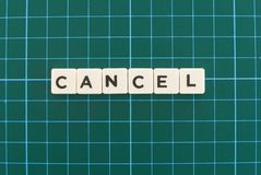 Cancel word made of square letter word on green square mat background stock photos