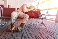 Canceled flight Man sleeping on his travel luggage. Inside airport terminal with back light bright sun coming throw window Stock Photos