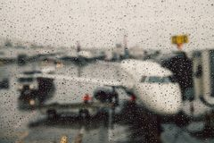 Canceled flight during weather conditions concept. Aircraft on gate under massive rain. Delay flight stock photo