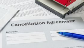 Cancellation agreement with a pen on a desk. A Cancellation agreement with a pen on a desk Stock Photography