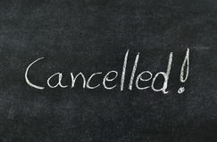 Cancelled on blackboard. Cancelled written with chalk on blackboard Royalty Free Stock Photos