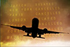 Cancelled flights. Commercial aircraft airborne against cloudy sky and timetable showing cancelled flights Royalty Free Stock Image