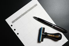 Cancelled planning, appointment, schedule, meeting concept. Business planning cancelled with blank calendar, pen and cancelled rub. Ber stamp on black background Stock Photography