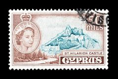 Cancelled postage stamp printed by Cyprus. That shows St Hilarion castle and portrait of queen Elizabeth, circa 1955 stock photography