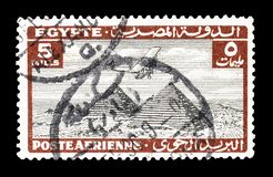 Cancelled postage stamp printed by Egypt. That shows Airplane over Giza pyramids, circa 1933 royalty free stock image