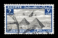 Cancelled postage stamp printed by Egypt. That shows Airplane over Giza pyramids, circa 1933 royalty free stock photography
