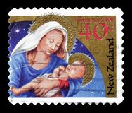 Cancelled postage stamp printed by New Zealand. That shows Christmas and depicts Madonna and child, circa 2000 stock image