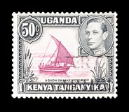 Cancelled postage stamp printed by Uganda, Kenya and Tanganyika. That shows A Dhow on lake Victoria and king George, circa 1938 stock photos