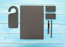 Cancelleria in bianco su fondo di legno Consista dei biglietti da visita, delle carte intestate A4, della penna e della matita Immagini Stock