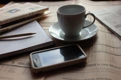Cancelleria con i giornali, lo smartphone e la tazza del cofee Fotografia Stock