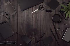 Cancelleria corporativa nera in bianco come posto di lavoro con lo spazio della copia su fondo di legno alla moda scuro Fotografia Stock