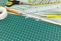 Cancelleria dell'ufficio o della scuola sulla stuoia di taglio: taglierina, matita, regola Immagine Stock Libera da Diritti