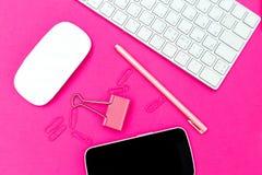 Cancelleria e tecnologia su fondo rosa di plastica Disposizione piana fotografia stock libera da diritti