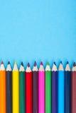 Cancelleria: matite colorate su fondo blu Immagini Stock Libere da Diritti