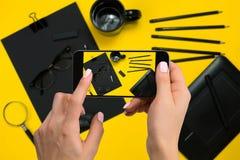 Cancelleria nera di fucilazione sulla macchina fotografica del ` s del telefono Cancelleria su fondo giallo Fotografia Stock Libera da Diritti